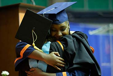 two graduates hugging