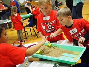Students participating in lesson study with sand and water
