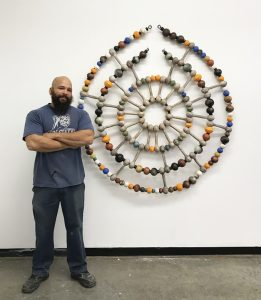 Sharif Bey stands in front of a piece of his artwork