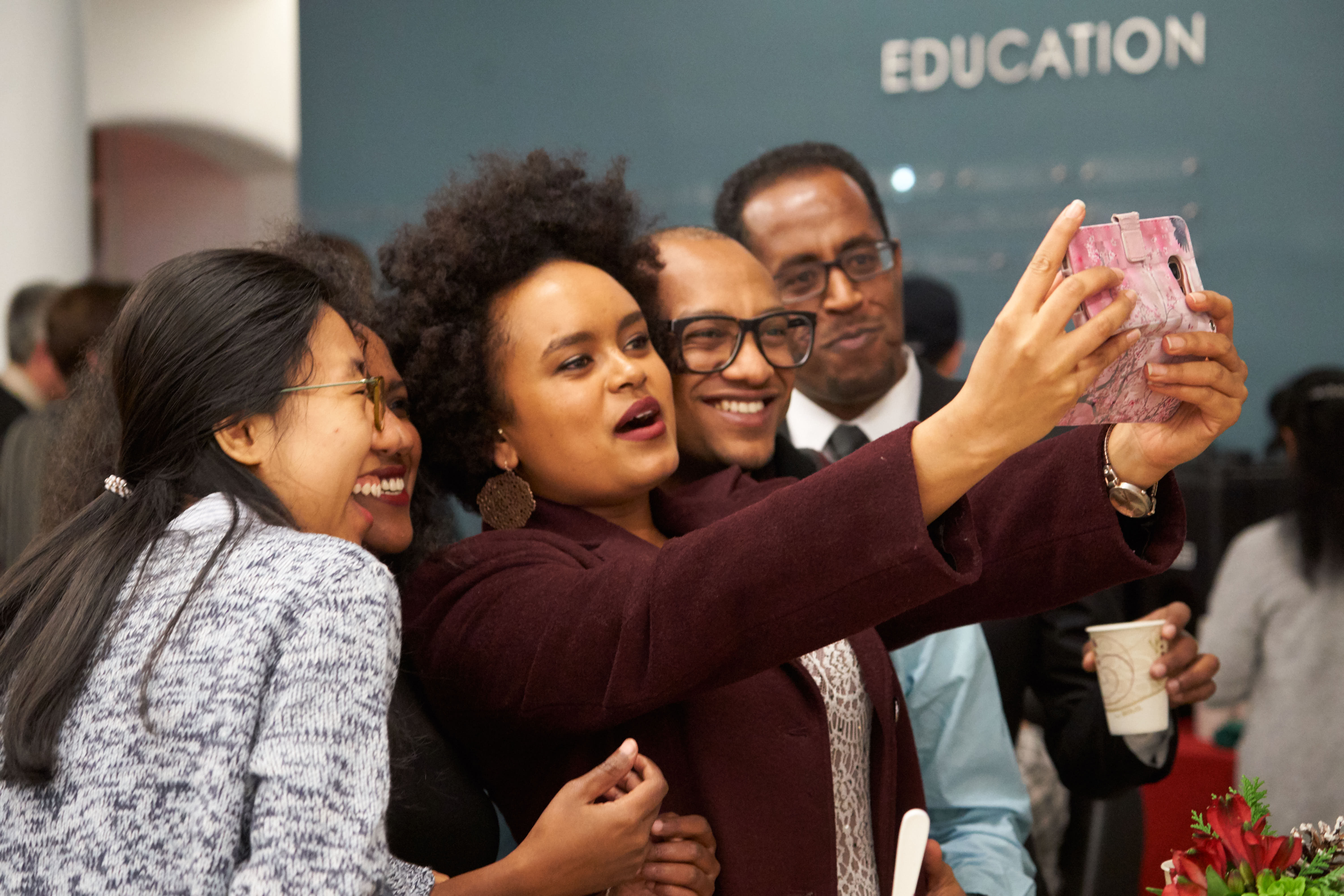 Four students take a selfie at their graduation reception