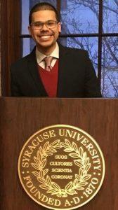Tyler Bell behind an S U podium