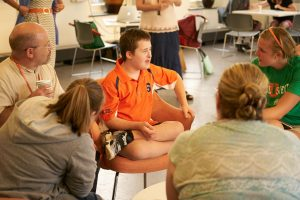 InclusiveU student sits with classmates in the commons