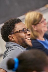 Male student of color smiles in class