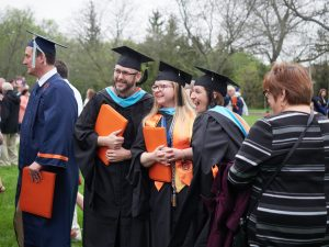 Master's students smile at graduation