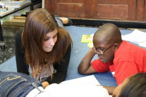 Student teacher and elementary school student sit on the classroom floor, reading