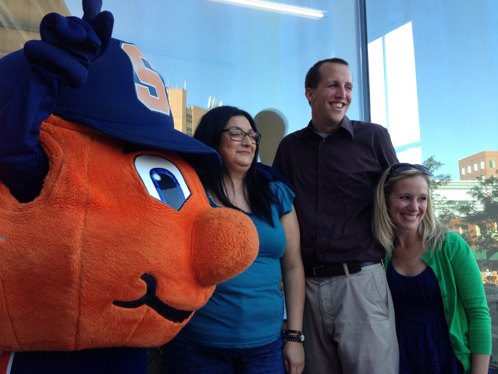 three students pose with otto the orange outside of huntington hall