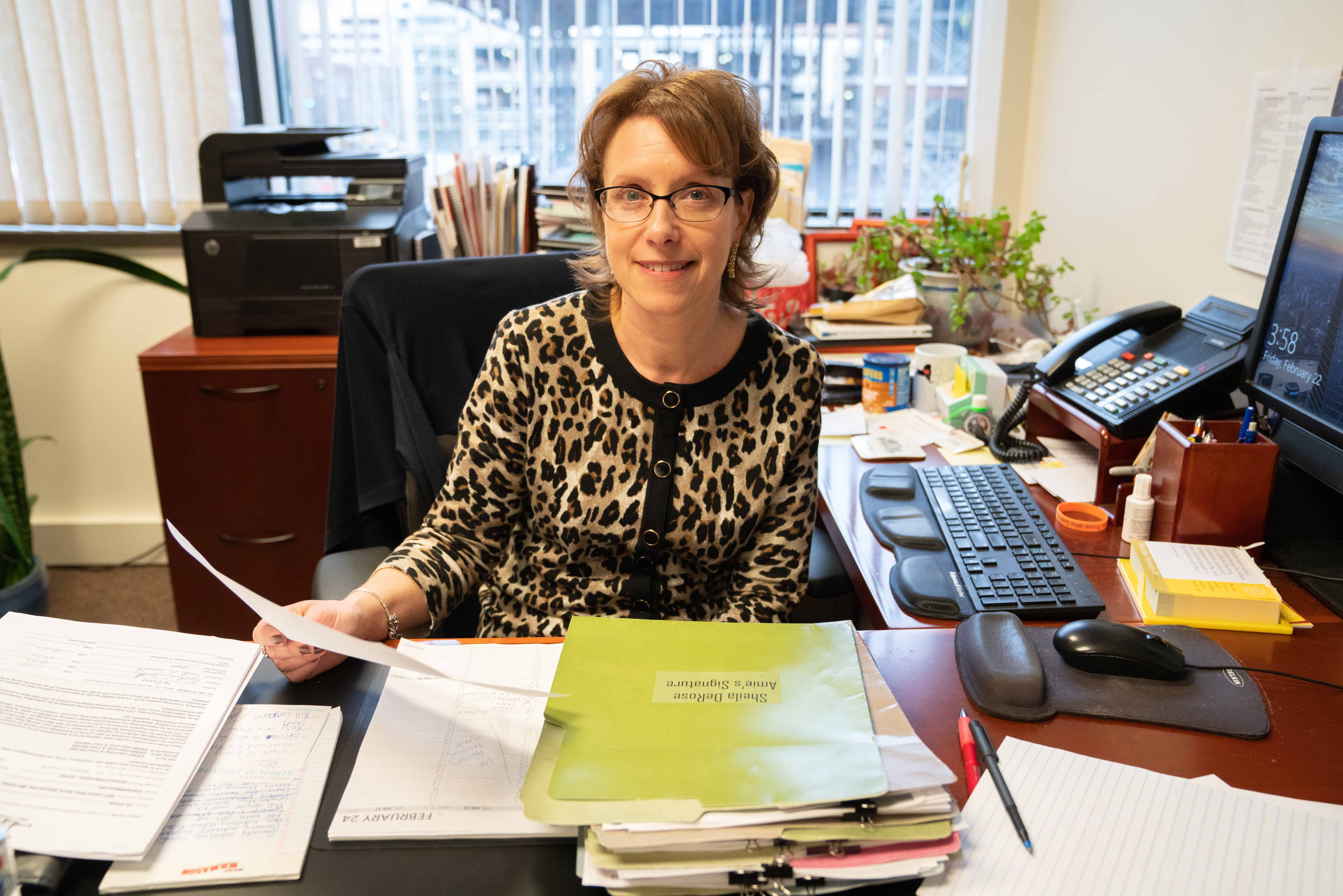 Amie Redmond at her desk, holding papers and folders