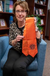 Amie Redmond holding a graduation stole given to her my a student
