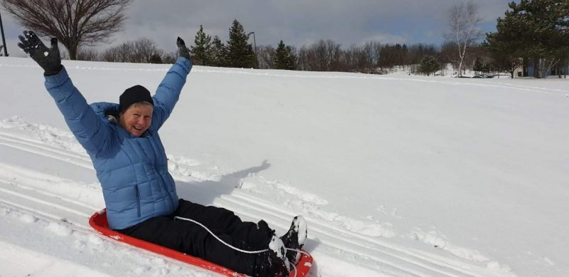 Dianne Christenson sleds down a snowy hill with her arms in the air