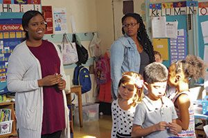 At The Neighborhood School in Manhattan, Dagmo Yusuf '17 (left) guides first-graders while accompanied by their teacher, Chelsea Crawford.