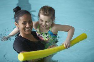 Exercise Science student works with a child in the pool during a Fit Families session