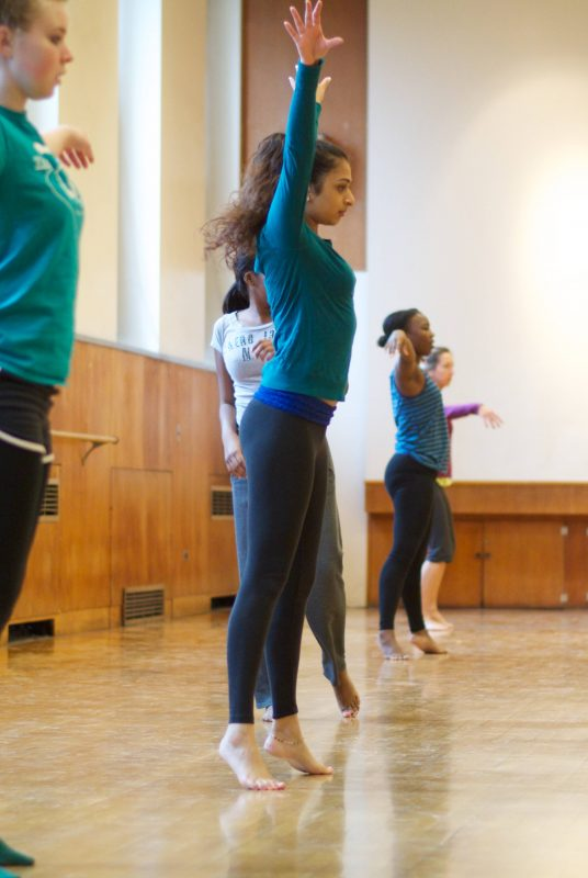 Five students stand on their toes with their arms in the air during a dance class