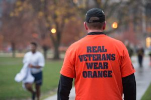 A man in a real veterans wear orange shirt walking on the syracuse quad