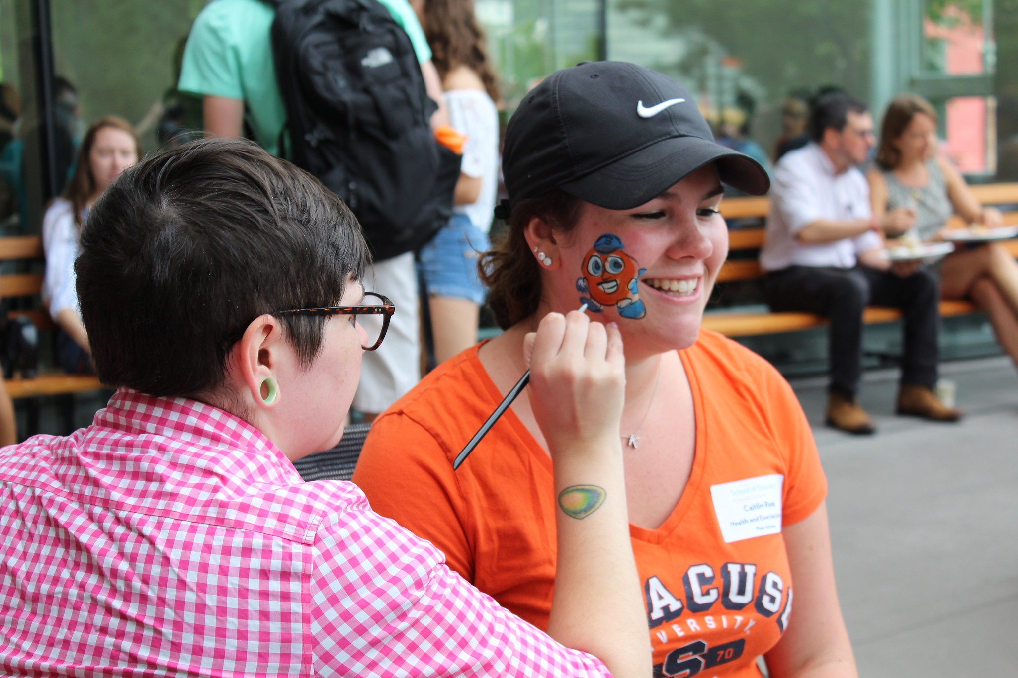 Student getting a picture of Otto the Orange painted on her cheek at the 2018 Welcome Back Picnic