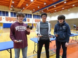 Three students in a school gym holding drones and controllers