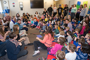 Music education students sitting on the floor leading a large group of preschool students sitting on the floor, as faculty and teachers watch standing in the back.