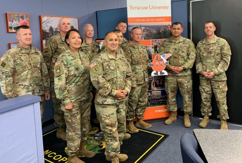 Sergeants Majors at Fort Bliss pose with a cutout of Otto The Orange in their Syracuse-themed remote distance education classroom