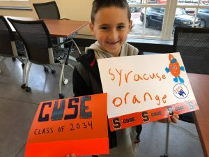 Child holding signs they made at the Inclusive U sign making party that say Syracuse Orange and Cuse class of 2034