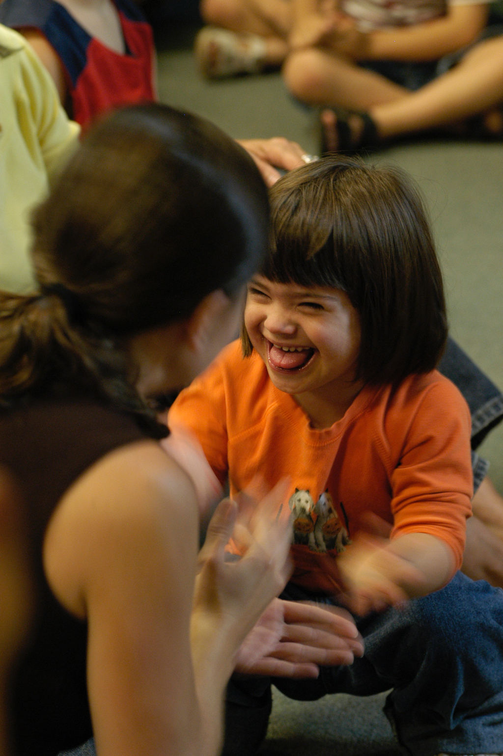 Kindergarten student with down's syndrome smiles at an student teacher in a classroom