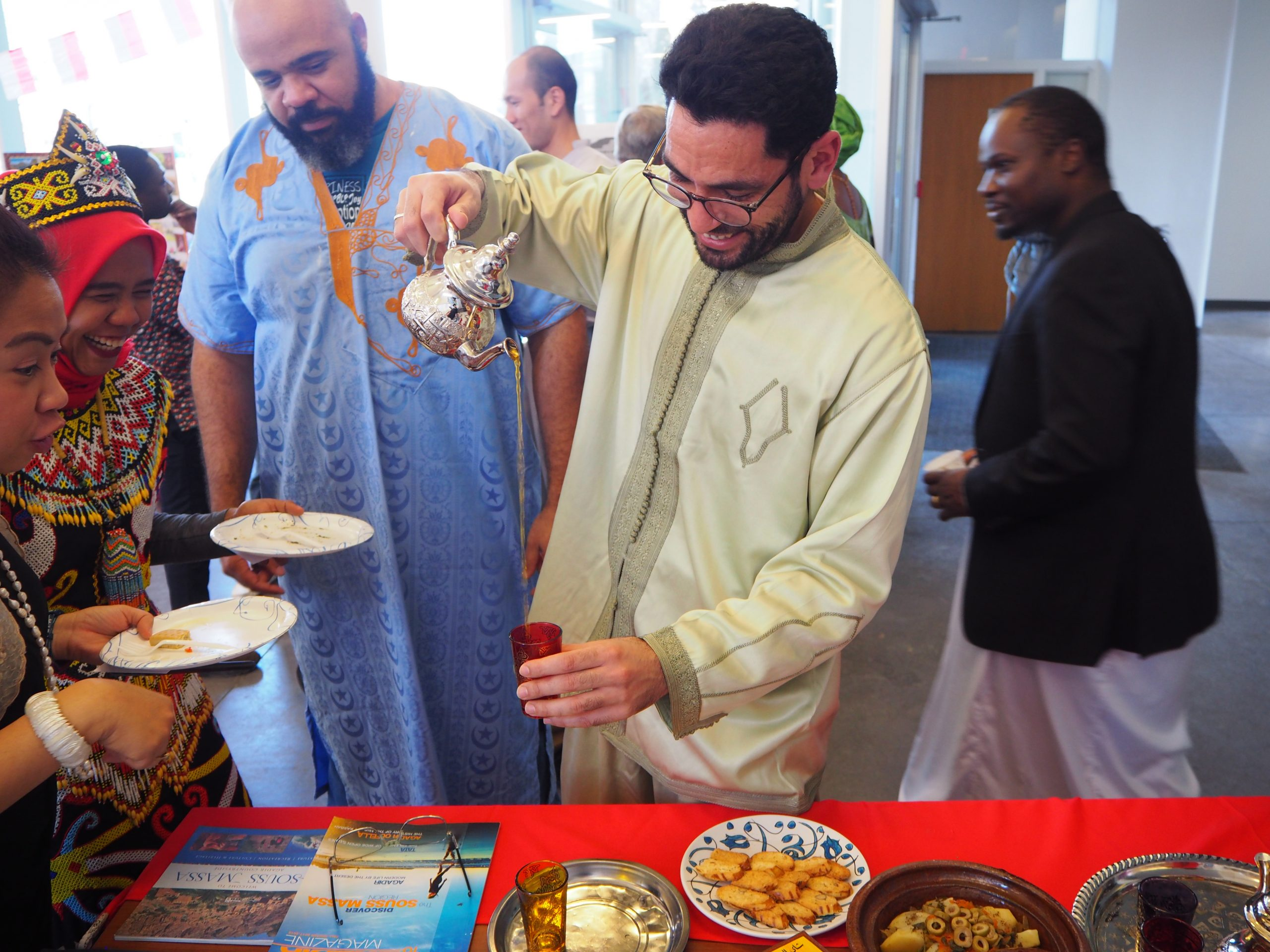 students pour tea at the international festival