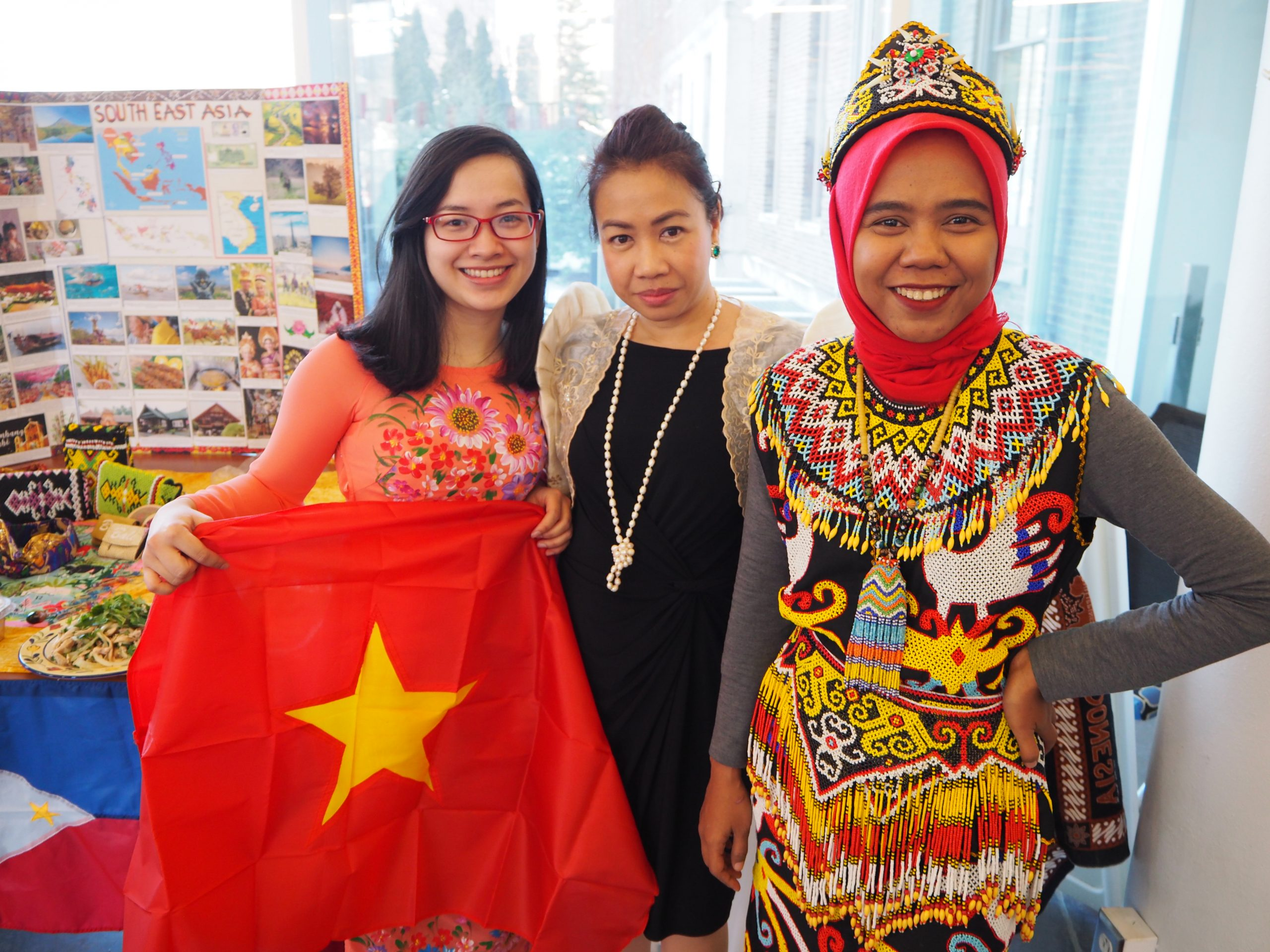 three students holding flags at the international festival