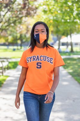 Savannah Stocker walks on the shaw quad, wearing a syracuse t shirt and orange and blue mask