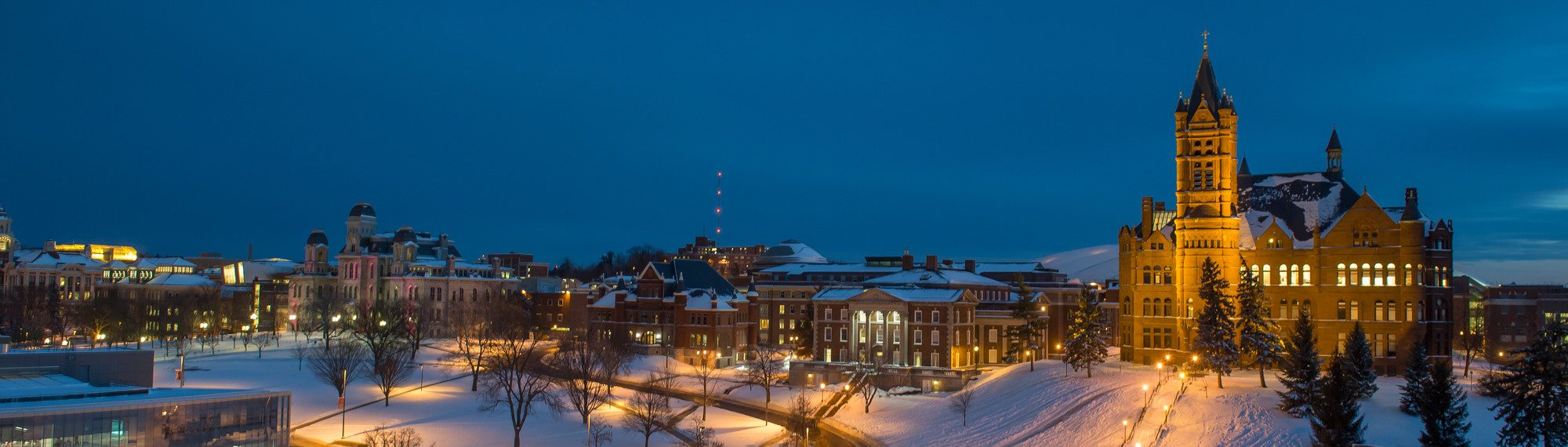 wide campus shot of crouse college, maxwell, eggers, and newhouse on a snowy night