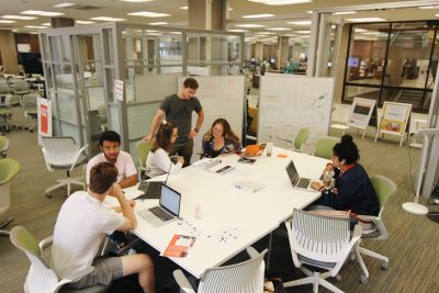 Students work around a table in the blackstone launchpad in bird library