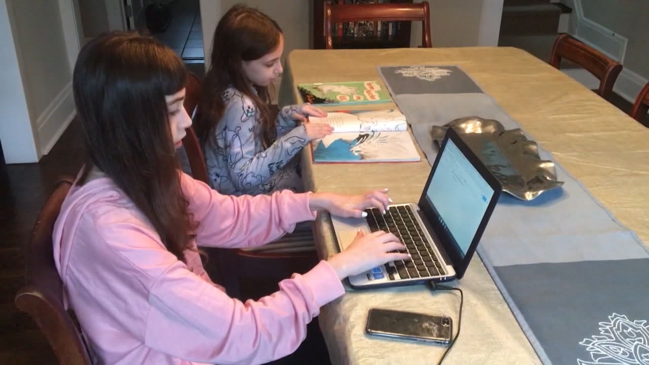 two students reading at a home kitchen table
