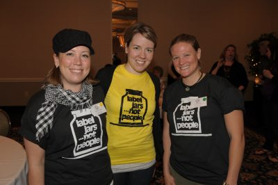 Three women wearing 'label jars not people' t shirts