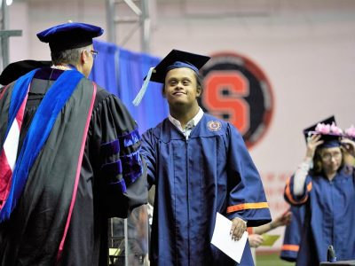 student crossing stage in cap and gown