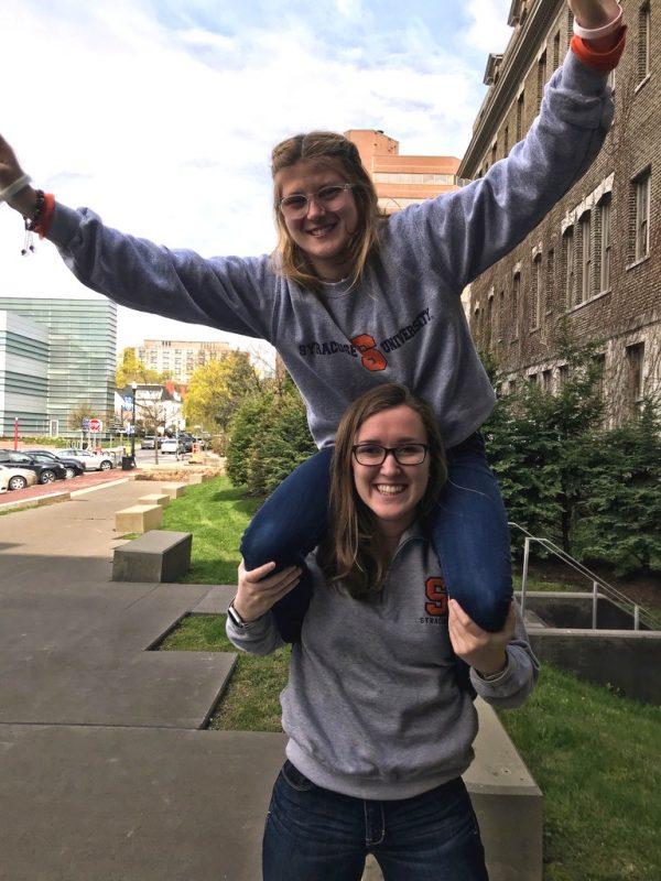 olivia posing on kylie's shoulders in matching syracuse sweatshirts