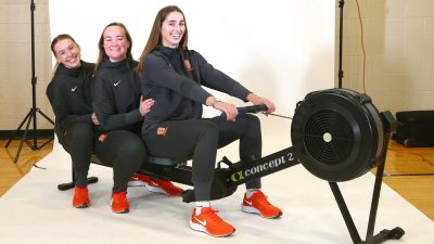 Lucy Pearce, Madeleine Holzman-Klima, and Maddy Horridge on a rowing machine