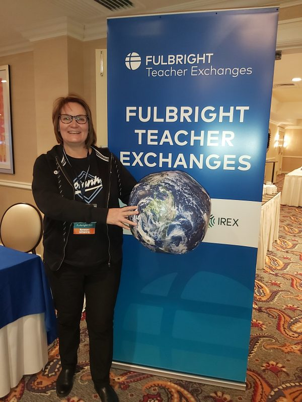 Tuija poses in front of a fulbright teachers banner