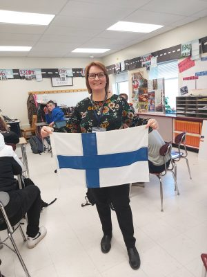 Tuija holds a finnish flag in an E S M classroom
