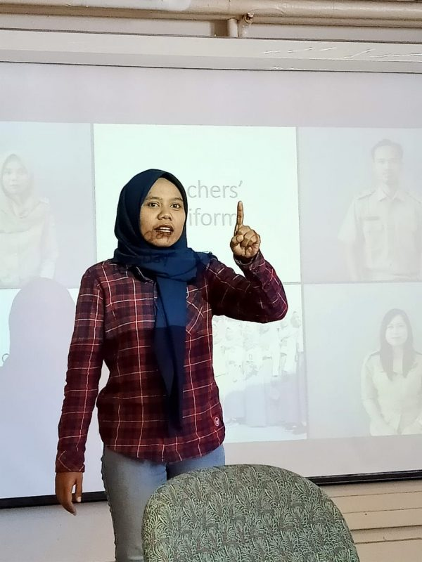 Yuli presenting at the front of a classroom